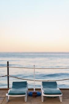 美しい穏やかな朝に木製の桟橋に2つの空の罪床。海の湾の観光埠頭