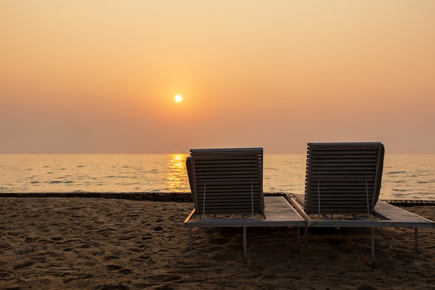 Two empty sunbeds on the beach against beautiful sunset over the ocean.