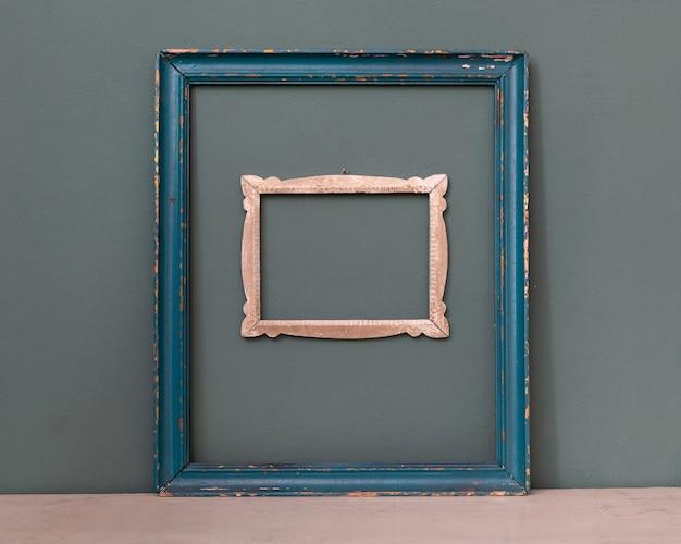 두 개의 빈 빈티지 액자, 하나는 파란색으로 칠하고 다른 하나는 실내 장식을 위해 청록색 벽에 매달려있는 작은 조각 프레임