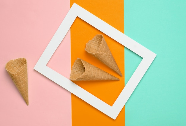 Two empty waffle horns in a white rectangular frame on a colored pastel background