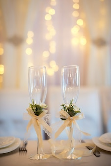 Two empty wedding champagne glasses with creamy bows and flower decor on the table.