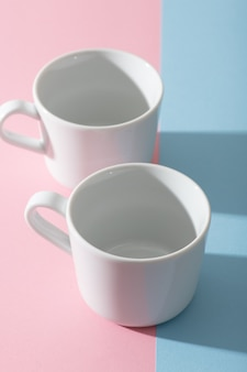 Two empty white cups on a pastel pink and blue background, photography with contrast shadow