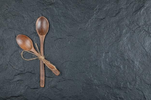 Due cucchiai di legno vuoti su uno sfondo scuro.