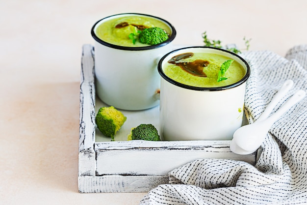 Two enamel mugs with healthy vegan broccoli soup with spicy oil and aromatic herbs. diet food concept.