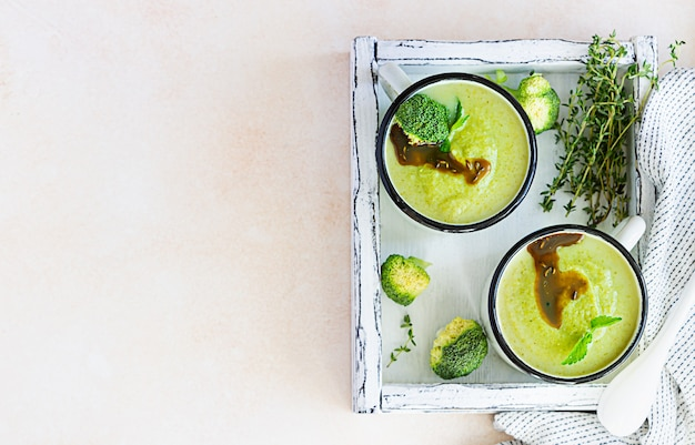 Two enamel mugs with healthy vegan broccoli soup with spicy oil and herbs. diet detox food concept.