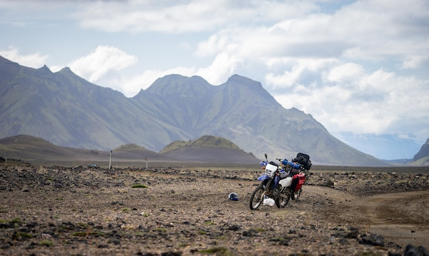Two enduro motorcycle standing on a dirt road in the desert surrounded by mountains on the laugavegur trail