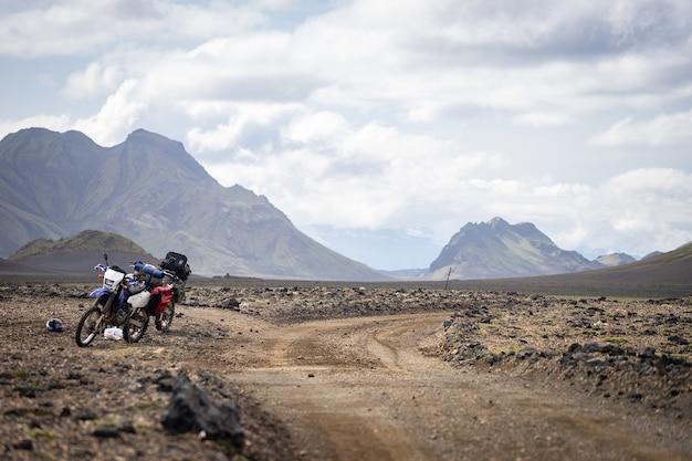 アイスランドのロイガヴェーグルトレイルの山々に囲まれた砂漠の未舗装の道路に立っている2台のエンデューロバイク。オフロード旅行のコンセプト、エンデューロライダーの装備、極端なライフスタイル。