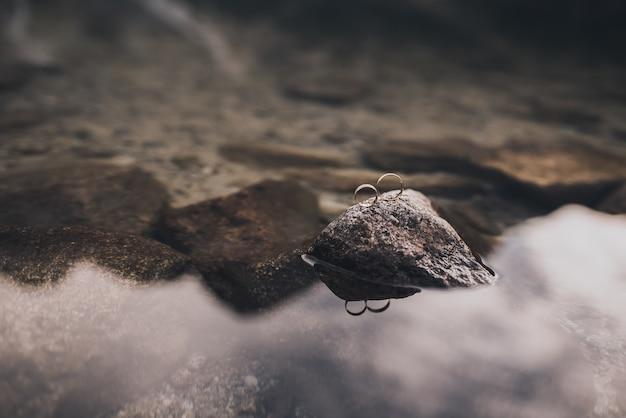 Два обручальных простых золотых кольца на подставке на сером камне кристально чистой воды