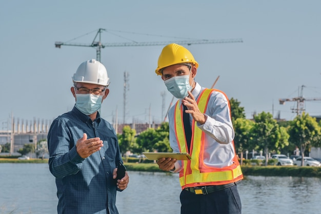 Two engineer in face mask talking project planing on site construction