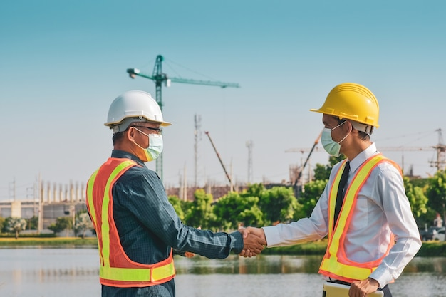 Two engineer shake hand on site construction