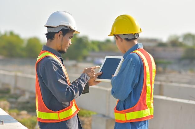 通信を話す2人のエンジニアが建設現場でタブレット検査を使用