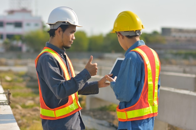 Two engineer talking communication use tablet inspection at construction site