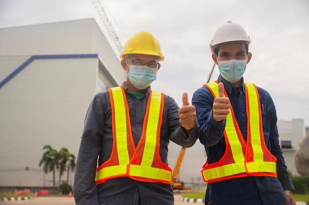 두 명의 엔지니어가 현장 건설에 성공을 거두었고, 두 사람은 의료 마스크를 착용하여 covid19 코로나 바이러스, 작업자 작업 건축가를 보호합니다.