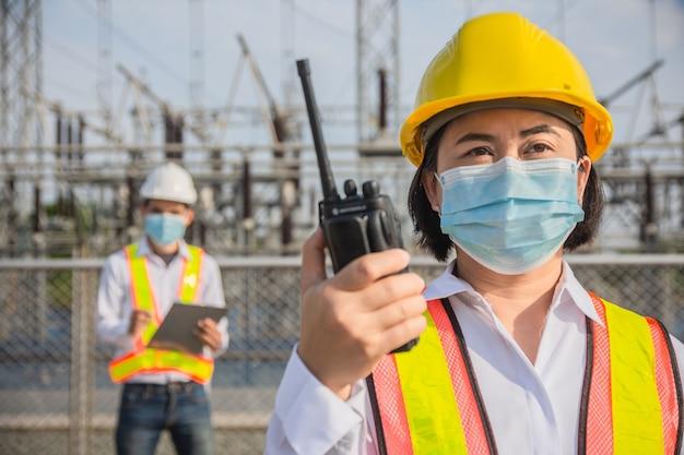 두 엔지니어 착용 안면 마스크 팀워크는 산업 전기 발전소, 팀워크 착용 마스크는 코로나 바이러스를 보호합니다