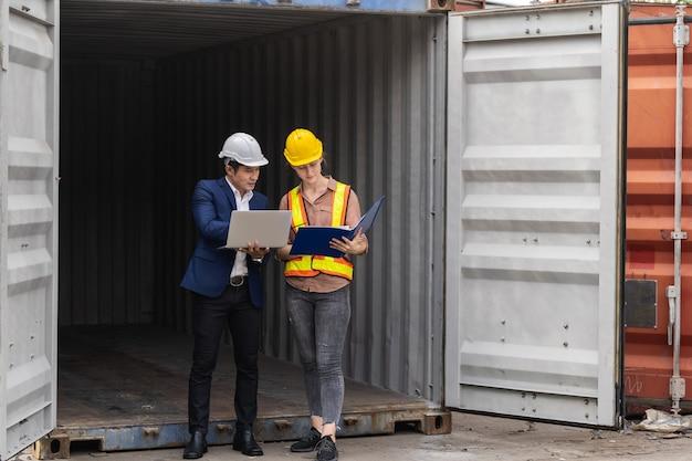 Два инженера-работника держат ноутбук, проверяя качество коробки контейнеров