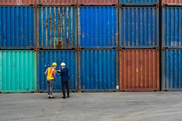 Два инженера держат ноутбук, документ для проверки качества коробки контейнеров с грузового судна для экспорта и импорта, синий фон контейнера