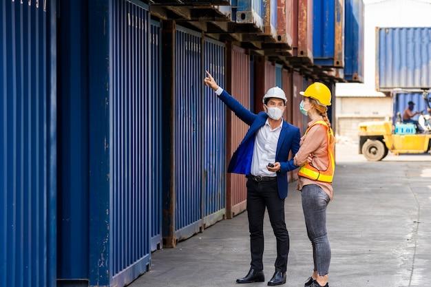 2人のエンジニア労働者がラップトップを持っており、輸出入用の貨物船からコンテナボックスの品質をチェックするためのドキュメント、青いコンテナの背景