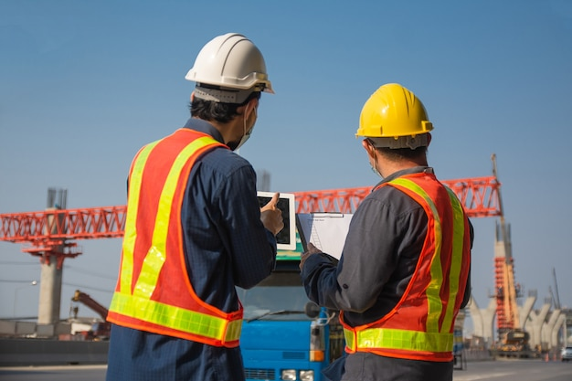サイトの道路建設に取り組んでいる2人のエンジニアワーカータブレット、アジア人男性建築ビルダー建築測量士
