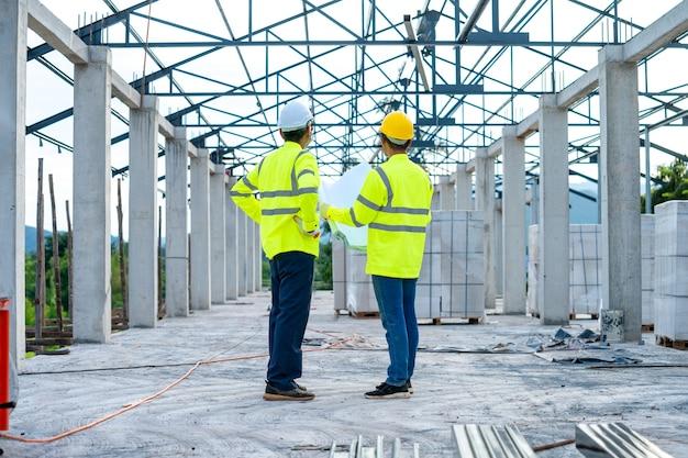 建築現場での製造工程をチェックする2人のエンジニア