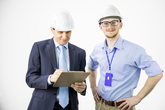 Two engineers different ages look at camera smiling, making notes on clipboard