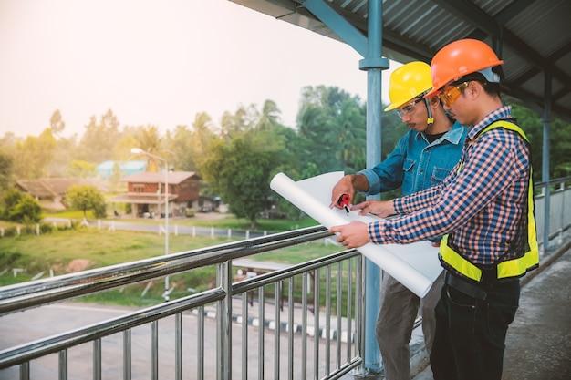 Two engineers standing on the bridge over the bridge.