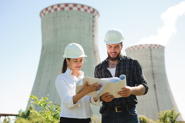 Two engineers standing at electricity station, discussing plan.