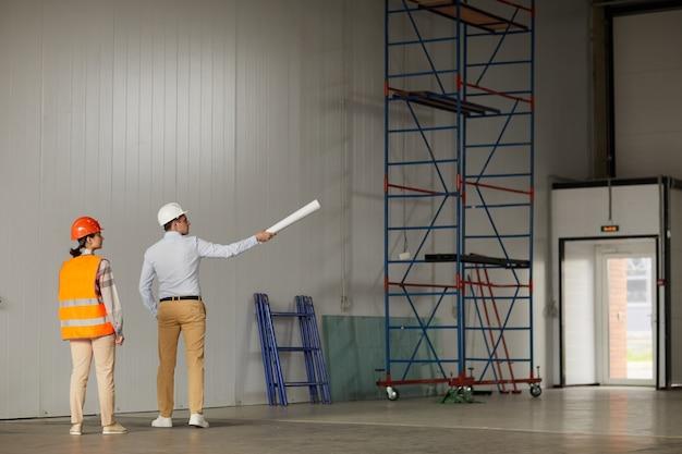 Два инженера стоят в пустом здании и обсуждают новый строительный проект