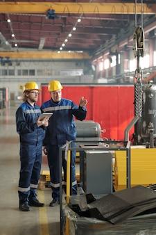 두 명의 엔지니어가 큰 작업장이나 공장에 서서 새로운 산업 장비나 기계를 가리키며 토론하고 있습니다.