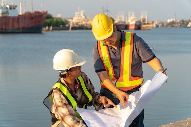 두 명의 엔지니어가 안전모를 쓰고 서 있었습니다. 부두에 서서 청사진을 들고 건설에 대한 계획을 참조하십시오. 효율적인 건설 관리의 개념입니다.