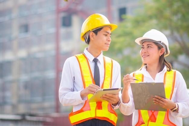두 명의 엔지니어가 태블릿을 사용하고 건설 현장에서 이야기합니다.