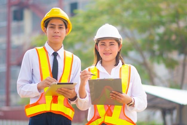두 명의 엔지니어가 건설 현장에서 태블릿을 사용합니다.