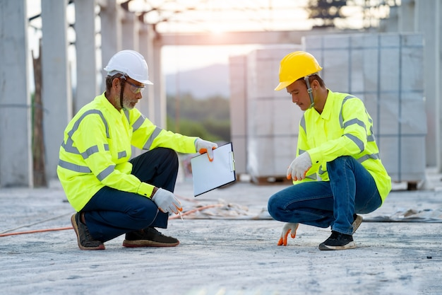 Two engineers with clipboard working at construction site