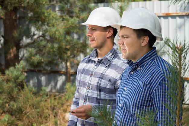 真面目な表情の2人のエンジニアが、フレームの左側で何かを見守っている建築現場に一緒に立っています