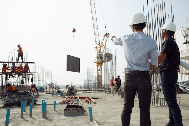 Two engineers work on the construction site