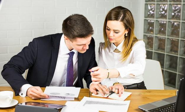 一緒に座っている2人の起業家がドキュメントを比較するオフィスデスクで働いています。