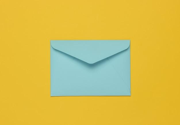 Два конверта голубого пастельного цвета на желтом фоне. плоский макет на день святого валентина, свадьбу или день рождения. вид сверху