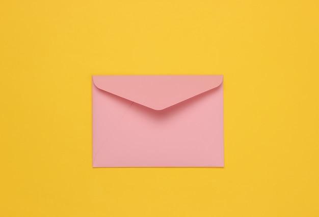 Два конверта розового пастельного цвета на желтом фоне. плоский макет на день святого валентина, свадьбу или день рождения. вид сверху