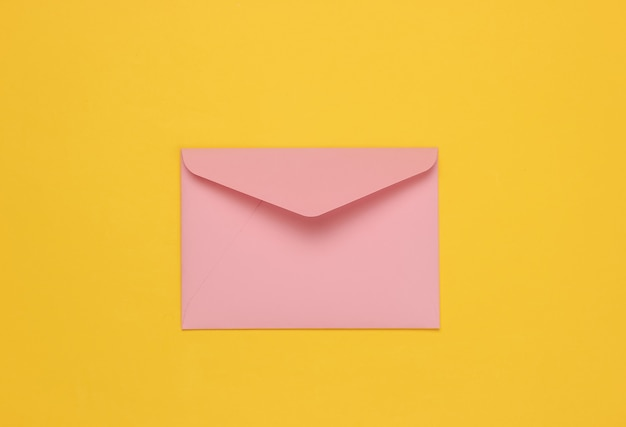 Two envelope pink pastel color on yellow background. flat lay mockup for valentines day, wedding or birthday. top view