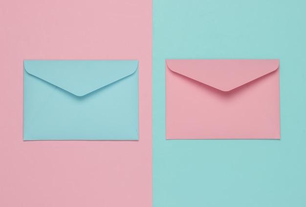ピンクとブルーのパステルカラーの2つの封筒。バレンタインデー、結婚式、誕生日のフラットレイモックアップ。上面図