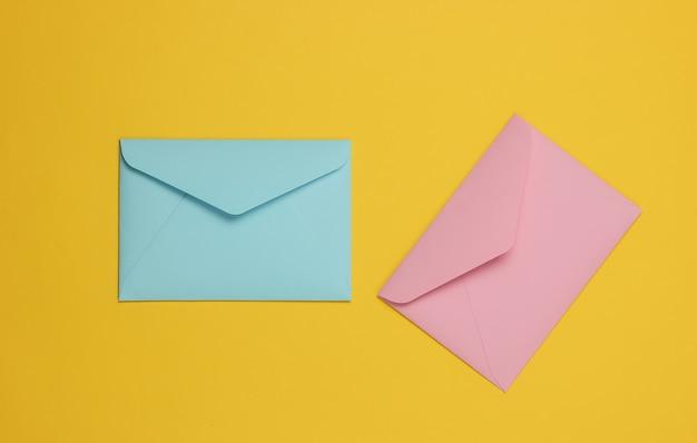 黄色の背景にピンクとブルーのパステルカラーの2つの封筒。バレンタインデー、結婚式、誕生日のフラットレイモックアップ