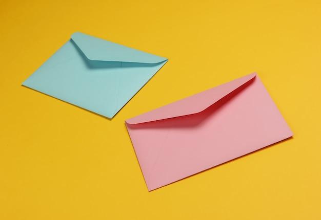 黄色の背景にピンクとブルーのパステルカラーの2つの封筒。バレンタインデー、結婚式、誕生日のモックアップ