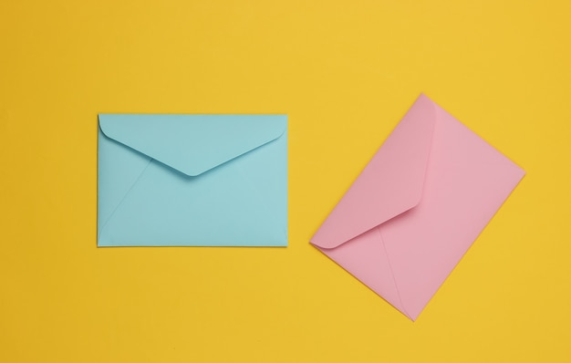 Two envelopes of pink and blue pastel colors on a yellow background. flat lay mockup for valentines day, wedding or birthday