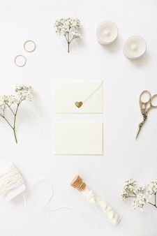 Two envelopes surrounded with wedding rings; candles; scissor; string; test tube and baby's-breath flowers on white backdrop