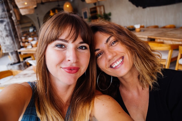 Two european caucasian woman friends with natural makeup and short hair take selfie in summer cafe
