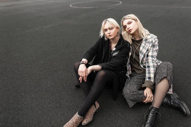 屋外のバスケットボールコートで休むトレンディなカジュアルな若者の服を着た2人のヨーロッパの元気な姉妹