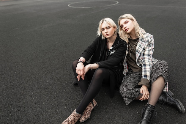 Two european fine sisters twin in trendy casual youth clothes resting on basketball court outdoors