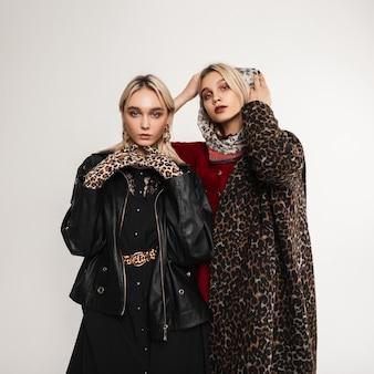 실내에서 매혹적인 유행의 옷을 입은 두 명의 유럽 유행 여자 친구