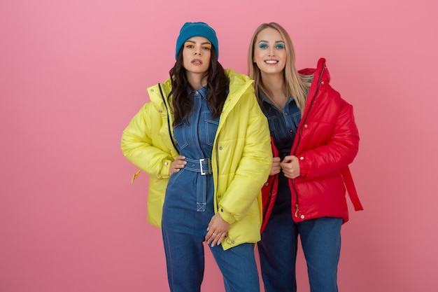 Two excited attractive girl friends active women posing on pink wall in colorful winter down jacket of bright red and yellow color having fun together, warm coat fashion trend