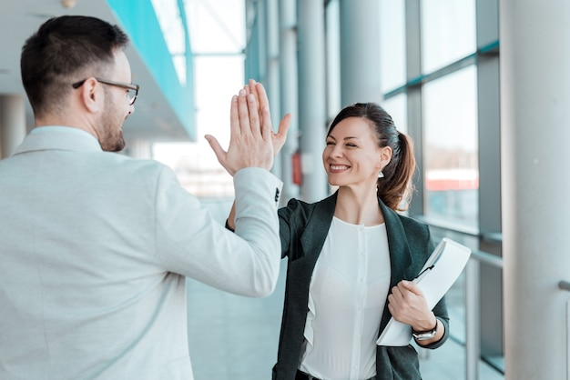 Two excited business colleagues team give high five.