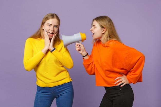 パステルバイオレットブルーの壁に隔離されたメガホンで鮮やかなカラフルな服を着た2人の興奮した陽気な若いブロンドの双子の姉妹の女の子が叫びます。人々の家族のライフスタイルの概念。 。